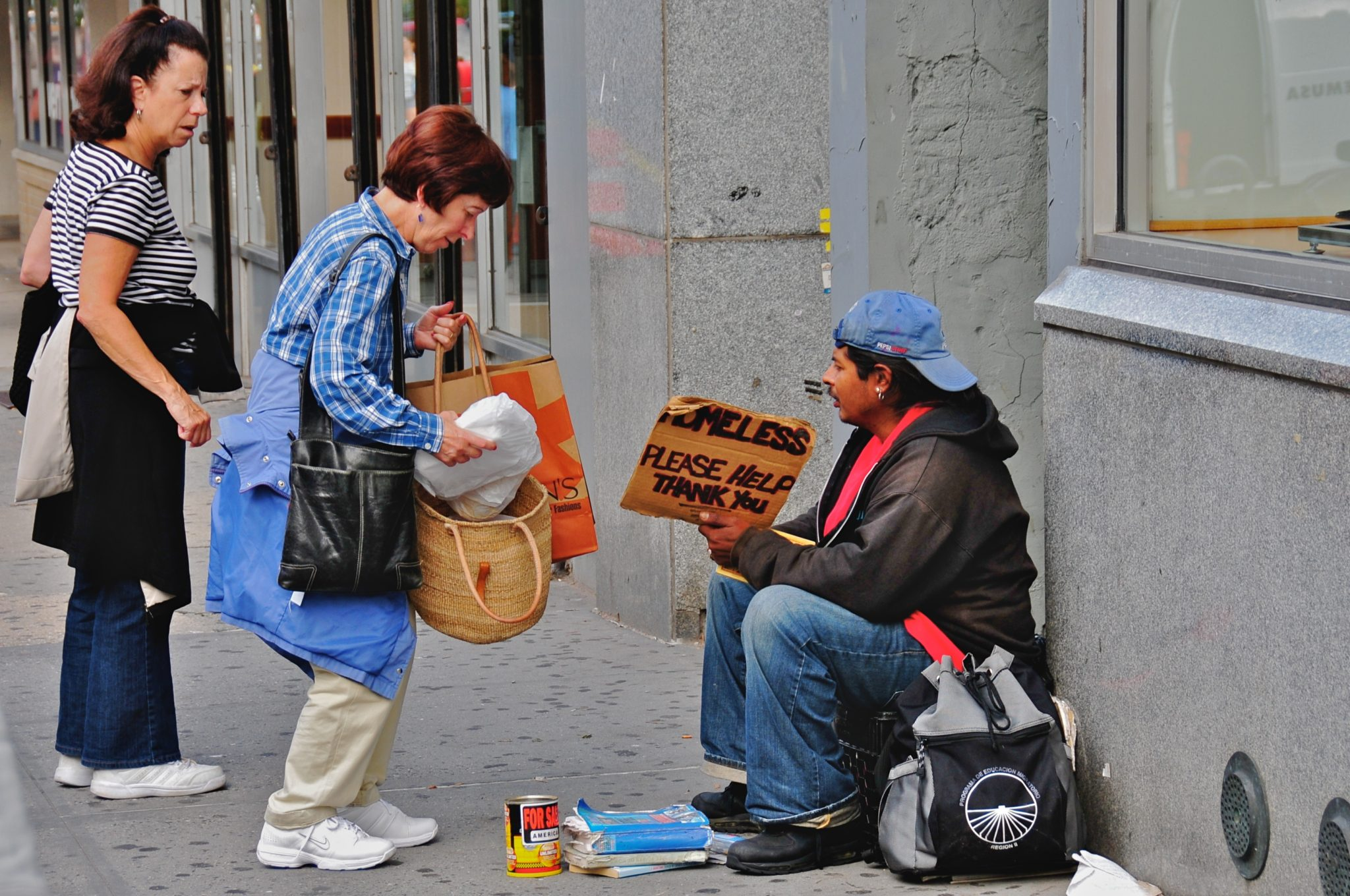 """This was taken about halfway up the block on the east side of Broadway, between 79th and 80th Street. It's at the north end of the """"Filene's Basement"""" store on the corner, and it's a place where I've often seen homeless people holding up a sign that asks for assistance... With very rare exceptions, I haven't photographed these homeless people; it seems to me that they're in a very defensive situation, and I don't want to take advantage of their situation. But something unusual was happening here: the two women (who were actually cooperating, and acting in tandem, despite the rather negative demeanor of the woman on the left) were giving several parcels of food to the young homeless man on the right. I don't know if the women were bringing food from their own kitchen, or whether they had brought it from a nearby restaurant. But it was obviously a conscious, deliberate activity, and one they had thousght about for some time... What was particularly interesting was that they didn't dwell, didn't try to have a conversation with the young man;they gave him they food they had brought, and promptly walked away. As they left, I noticed the young man peering into his bag (the one you see on the ground beside him in this picture) to get a better sense of the delicious meal these two kind women had brought him... ********************** This is part of an evolving photo-project, which will probably continue throughout the summer of 2008, and perhaps beyond: a random collection of """"interesting"""" people in a broad stretch of the Upper West Side of Manhattan -- between 72nd Street and 104th Street, especially along Broadway and Amsterdam Avenue. I don't like to intrude on people's privacy, so I normally use a telephoto lens in order to photograph them while they're still 50-100 feet away from me; but that means I have to continue focusing my attention on the people and activities half a block away, rather than on what's right in front of me. I've also learned that, in many c"""